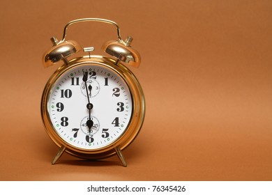 Nice golden alarm clock on brown background with copy space