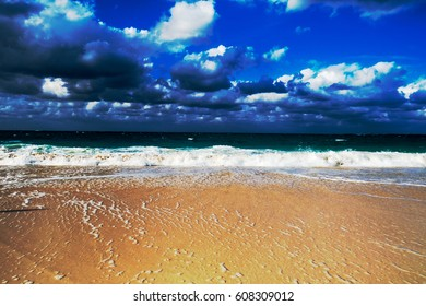 A nice golden beach view of the ocean with lot of clouds in the sky. New Providence, Nassau, Bahamas.
