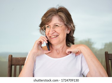 Nice grandmother with glasses is talking with her friend through her smartphone on a sunny day
