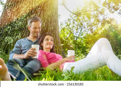 A nice grey hair man and a woman are sitting in the grass, having hot take away drinks. The man is sitting against a tree while his girlfriend is laying against him. They are relaxing.