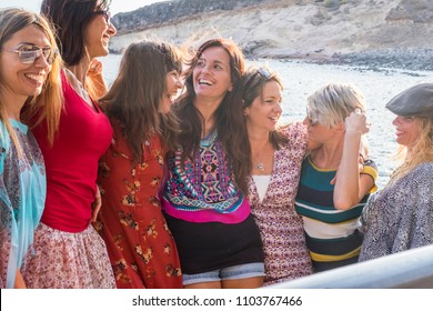 nice group of happy young females stay together near the beach and ocean in summer leisure activity, smiles and laugh all together in friendship hugged with lovely relationship.  vacation