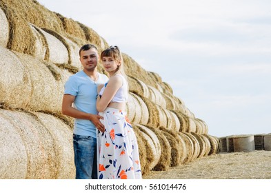 Nice guy and his pregnant girl on a field with round bales of hay in summer. Charming young couple on a photo shoot in summer.