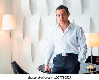 Nice guy in a white shirt in an interior in high-tech style