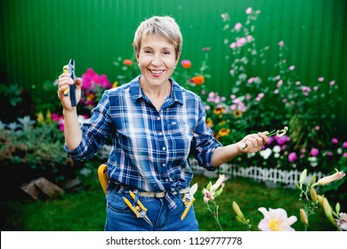 nice happy woman aged retired gardener holding a working tool in a nail clipper / trimmer and smiling