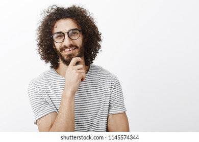 Nice idea, you intrigued me. Portrait of interested smart handsome adult man with beard and curly hair in trendy glasses, smiling curiously and rubbing chin while having great thought over gray wall