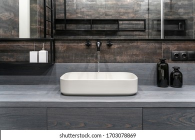 Nice illuminated modern bathroom with textured bronze tiled walls. There is a gray stand with drawers and a white sink, dark matte faucet with flowing water, black bottles, wide mirror, shelves.