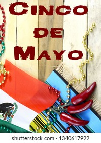 Nice image for Cinco de Mayo, a Mexican celebration, on the 5th of May. Red, green and gold beads with Mexican flag and red chilis on a wooden background. Vertical image with text added.