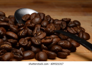 NIce image of Delicious Coffee Beans on Wooden Background with a Metal Spoon