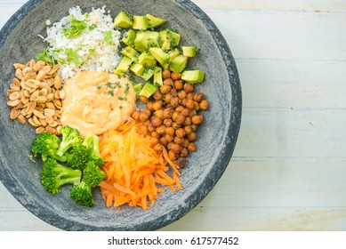 Nice image of a fresh salad in a bowl on a wooden table.