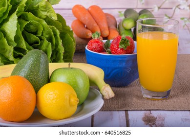 Nice image of a healthy fruit and vegetable juice surrounded by fruits and vegetables.