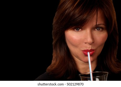 Nice Image of a Middle aged woman sipping out of straw