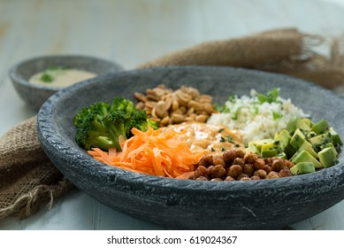 Nice image of a mixed salad in a Buddha bowl on a wooden table with a bowl of sauce on the side.