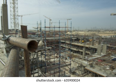 Nice image of scaffolding on a construction site with cranes in Dubai.