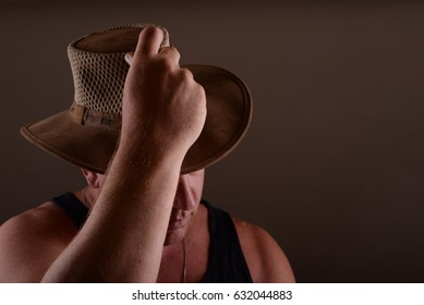 Nice image of a young male tilting a western style cowboy hat in greeting.