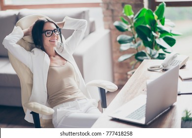 Nice, independent, cute woman in white suit, formal wear, glasses sitting on chair at her desk in office, holding arms behind the head with close eyes, thinking about holidays, vacation