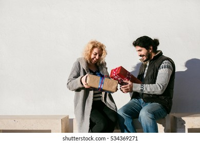 nice joyful couple standing outside on a bench and exchanging gifts