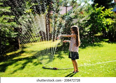 Nice kid girl with long hair has fun with garden sprinkler playing with water splashes in the backyard on a sunny hot summer  evening.