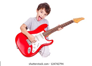 Nice kid playing a red guitar on the floor with his tongue out. The child is isolated on white.