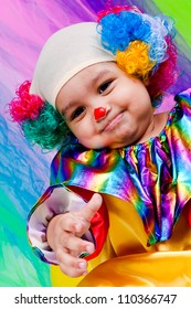 A nice kid wearing clown clothes and hair. The boy is very happy on a colorful background. The toddler is on the floor with some toys.