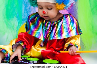 A nice kid wearing clown clothes and hair. The boy is very happy.