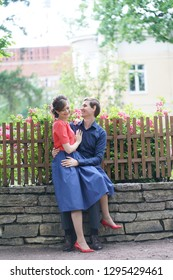 nice kind adult couple walking in the green summer garden, hug, smile and kiss in love