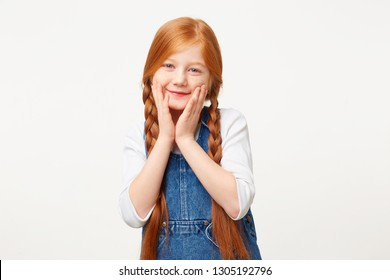 Nice kind girl with braided red hair in two long plaits, smiling affably and keeps palms on a face, dressed in jeans overall dress over a white longsleeve isolated on white background