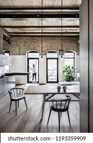 Nice kitchen in a loft style with brick walls, wooden ceiling and a parquet on the floor. There is a wooden table, metal lockers, sink, dark tabletop, chairs, plant, woman near glass door to balcony.