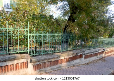 a nice laced fence aside the road at a calm town street