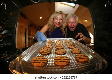 A nice lady bakes Cookies for her favorite pool man as a special Thank You. Shot from inside the oven out for a unique view. Focus on the cookie with the people slightly out of focus.