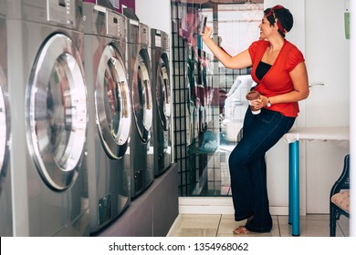 Nice lady with red shirt enjoy technology using smartphone while automatic laundry wash and dry her clothes - modern lifestyle ofr urban girl