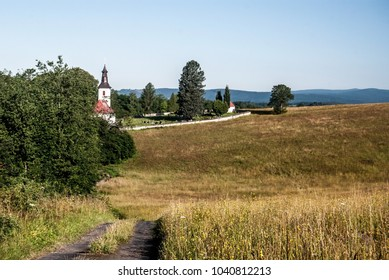 nice landscape above Prostredni Lipka village in Czech republic with church, cemetery, meadow, trees, hills on the background and clear sky