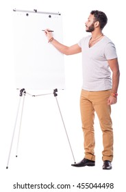 Nice latino cutout man writing on flip chart profile view. Dressed in beige pants and grey t-shirt. Full length portrait isolated on white background.