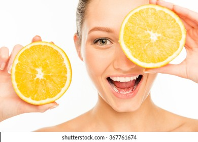 Nice laughing girl with orange slices in front of her eye
