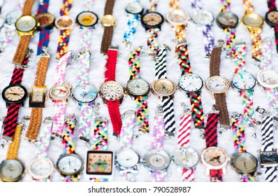Nice layout of many colorful watches on a white surface.