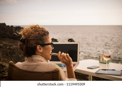 Nice lifestyla for beautiful caucasian woman working in alternative office place. outdoor in front of the ocean. digital nomad and internet work for modern possibilities and freedom closed spaces.