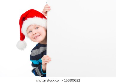 Nice little boy looking over white wall. Smiling isolated over white background