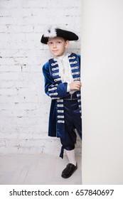 Nice little boy wearing blue musketeer costume posing near the wall