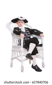 Nice little boy wearing old-fashioned clothes posing in the chair. Isolated on white