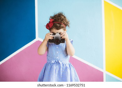 Nice little girl with dark curly hair in dress playfully covering face with retro camera and taking photos over colorful background. Family values