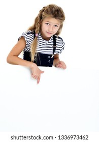A nice little girl points a finger at a large white banner on which you can write any advertisement. The concept of promotion of goods, happy childhood. Isolated on white background.