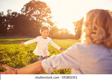 Nice little girl run to mother's hug in nature