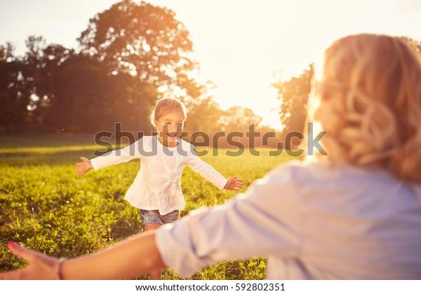 Schönes kleines Mädchen, das in der Natur zu den Umarmungen der Mutter führt