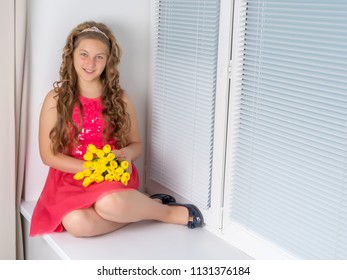 A nice little girl sits on a window sill with a bouquet of tulips. The concept of happy people, spring vacation.