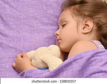 nice little girl sleeping in her bed at home