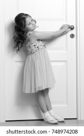 A nice little girl is standing by the door. The concept of family happiness and a home.