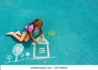 Nice looking black girl drawing house sun and trees with chalk on playground