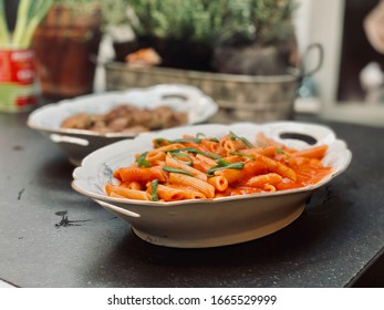 Nice looking bowl with Italian pasta and red sauce in kitchen.
