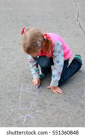 Nice looking caucasian little girl drawing house with chalk on playground