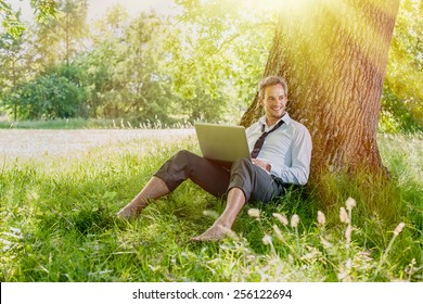 A nice looking grey hair man is sitting against a tree in the grass, looking at his computer. He is relaxing, enjoying the shadow of the tree in a sunny day.