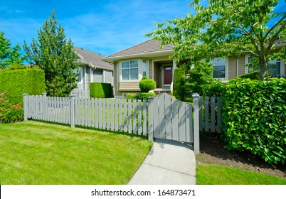 Nice looking house behind the wooden fence at the empty street in the suburbs of Vancouver, Canada.